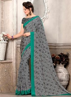 Precise splendor comes out as a result of the dressing style and design with this Black, White & Teal Blue saree. This pretty attire is displaying unbelievable print work. Comes with matching blouse.