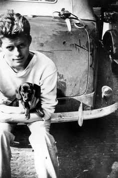 """John F. Kennedy, 20 years old, during his tour of Europe in the summer of 1937. In his arms is """"Dunker"""" the dachshund. Photo taken in The Hague, August 1937."""