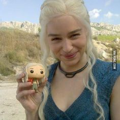 Emilia Clarke with her GoT action figure (Game of Thrones actors posing with their Funko toy counterparts)