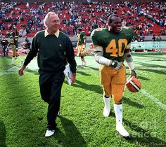 """Photograph of Jackie Parker after winning his first game after being named the new head coach of the Edmonton Eskimos in 1983 in a game against the Hamilton Ti-Cats. Along side is Edmonton Eskimos linebacker James """"Quick"""" Parker celebrating the victory."""
