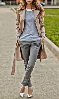 Thats an elegant smart-casual look. We see a beige trench-coat worn atop grey colored separates.