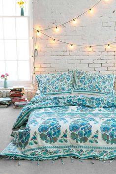 chambre bohème avec mur de brique blanche, guirlande lumineuse et literie blanche à motifs floraux bleus