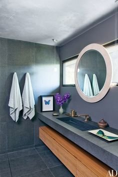 The guest bath is clad in basalt tile from Creative Environments; the mirror is by Paul Marra, and the towels are by Waterworks | archdigest.com