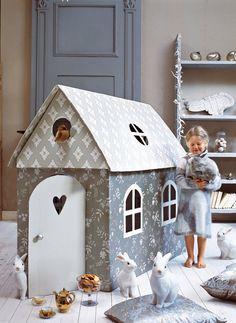 Une cabane pour enfant en carton recouverte de papier peint gris à motif