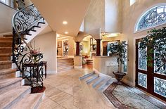 Now THIS is a foyer! I love the detail in the stair railing & the rug matching the shape of the stairs.