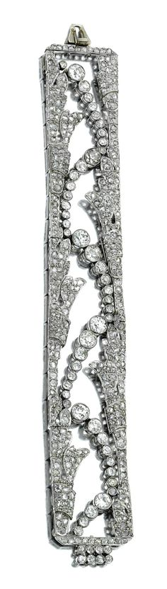 DIAMOND BRACELET, CIRCA 1915. Of open work design, set at the centre with an undulating line of claw-set circular-cut diamonds, to the rose-cut stone borders, length approximately 180mm.