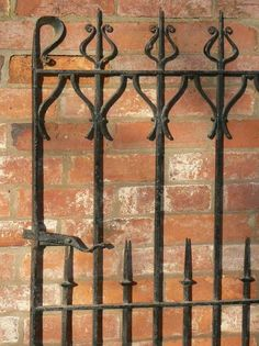 """An old iron garden gate, elegantly constructed with upright scrolled finials and a close spaced lower section. It is ex barn condition and was reputedly formerly in the grounds of Thurnby Manor, Leicester. late 19th Century/ Early 20th Century 41"""" wide x 59"""" high £395"""