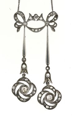 This necklace features diamonds mounted in silver and a stunning Georgian design. The top of the pendant is a lovely bow, and from that bow hangs to dangling silver drops with a flower design. The piece is mounted with 4 old mine cut diamonds which weigh a total of .85 carat and 68 rose cut diamonds which weigh a total of 1.00 carat. [They say it's Georgian. Looks more Edwardian to me.]