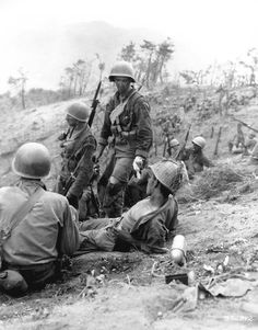 Hit in the back during a grenade duel, Corporal Dominick F. Zegarelli, (Utica, N.Y.) Company L, 7th Regimental Combat Team, U.S. 3rd Infantry Division, waits for evacuation, while other members of his platoon rest.  3 July 1951.  Korea.  Signal Corps Photo #8A/FEC-51-23550 (Brigham)