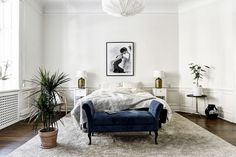 Minimalist inspired bedroom with a white pendant light, a large area rug, and a blue velvet bench