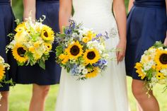 Rustic Southern wedding describes this wedding to a T with bridesmaids in navy blue, carrying sunflower bouquets, and groomsmen in seersucker suits.