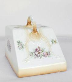 Antigua tapa quesera de cerámica con relieves y dibujos de flores.