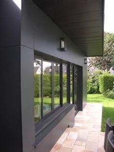Extension d'une maison pour un atelier d'artiste ouvert sur le jardin: ossature bois et bardage en panneaux composites Agence ArchiTK (Le Rheu 35)