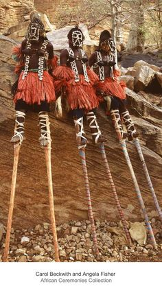 Africa | Masked Dogon stilt dancers rest against cliff-side before festivities.Their dance of flapping arm movements imitate a long-legged water bird. Mali, Middle Niger region. | ©Carol Beckwith and Angela Fisher