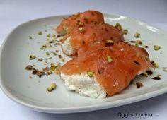 Gli involtini di salmone affumicato, ricotta e granella di pistacchi sono un antipasto semplice da preparare, può essere un'idea per il pranzo di Natale.