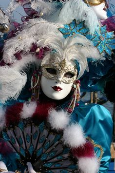 A Venetian costume and mask, shades of blue with white fur.