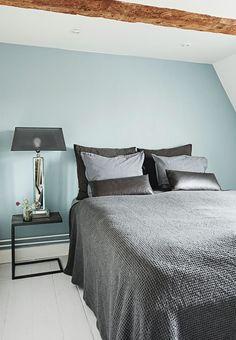 Soveværelse med lyseblå endevæg og grå nuancer på puder og sengetæppe