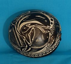 This is a nice example of a half (tree) gourd that has been covered with black pigment. The design of interlocking fish and other sea creatures is incised through the pigment. This was made by a young master carver from Pinotepa de Don Luis Oaxaca named Olegario Hernandez.  Sr. Hernandez had come to Oaxaca to demonstrate gourd carving and sell his works at the APPO cultural festival in February 2009