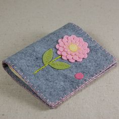 This handmade needle book features a pink and yellow dahlia flower with a green stem and leaves hand embroidered on a background of gray wool blend felt. Its the perfect way to organize your pins and needles. Embroidery was done by hand with 100% cotton embroidery floss. It has four ivory wool felt pages and a pink snap closure to keep your sewing supplies secure and tidy. The edges of the book were finished with a blanket stitch in matching pink embroidery floss. Size: 4 x 4 1/2 (10....