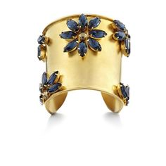 Light Gold and Montana Blue Flower Cuff from JANIS SAVITT.  Antique Light Gold and Crystal Flower Cuff Metal: Gold plated Stone: Swarovski crystal Width: 2 1/2 inches Diameter: 2 3/8 inches