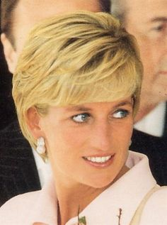 Diana ~ Princess of Wales wearing a light pink suit and huge oversized pearl and diamond earrings on and her ubiquitous pearl necklace.