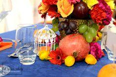 """Kolorowe dekoracje stołu weselnego w całości wykonane przez Agencję Ślubną Sroczyńskich """"Ślub Ręcznie Robiony"""". Bukiety z różnych kwiatów (róże, goździki, gerbery, mini piwonie) i owoców (winogrona, śliwki, cytryny, granaty etc), pomarańczowe serwetki, granatowe obrusy. Winietki w mandarynkach, dekoracje quilling'owe, białe latarenki."""
