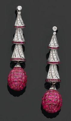 Paire de pendants doreilles formés d'une chute de clochettes retenant une pampille piriforme ornée de cabochons de rubis «goutte de suif» en serti invisible. Monture en or gris sertie de diamants brillantés et rubis calibrés. Hauteur: 5 cm. Poids: 19,5 g