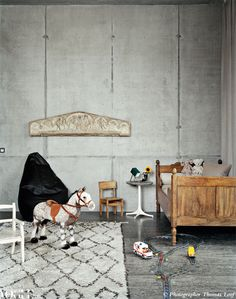 Concrete in a nursery? Yes, with several warm touches—wood, antique accents—throughout