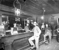 Bar patrons, holding beer and resting their feet on the barrail or nearby chairs, stand at a bar in Central City, Colorado. One patron smokes a cigar; another stands over a spittoon. The bartender stands behind the bar wearing a waistcoat and an apron; a little boy stands at the end of the bar.  [between 1870 and 1880]