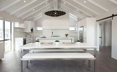 Sleek dining table with kitchen behind, in this open plan space.