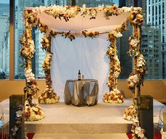 A traditional chuppah is embellished with natural wood wrapped with blooming roses and orchids in white, pink, yellow and orange.
