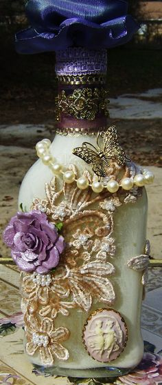 Altered bottle, embellished with scraps of lace & beads + this post has a lot of great ideas on how to reuse glass bottles.