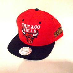 Manufactured by Mitchell & Ness, this Hardwood Classics Flat Bill Chicago Bulls limited item features a black cloth flat bill with a red cap. This is a 1996 NBA Finals Edition Hat. The back features an adjustable snap strap. On the front you will find the Chicago Bulls team logo embroidered in thick premium thread with the signature Mitchell & Ness logo embroidered in white in the back. The side features the 96' NBA Finals logo embroidered in premium thread. IN STORE ONLY!
