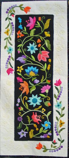 I like the use of the black background fabric for this appliquéd table runner.