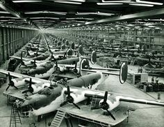 "B-24s in the Consolidated-Vultee Plant, Fort Worth, Texas–the other Liberator Plant. In foreground are Liberator bombers while to the rear of this front line are C-87 ""Liberator Express Transports"" in various assembly stages. The second line is composed entirely of B-24 Liberator bombers in final assembly stages. Photo via Hometown by Handlebar Blog"