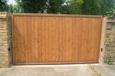 Simple flat top sliding gate design with automation. Constructed using slow grown, redwood pine with a medium oak stained finish.