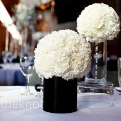 Black tablecloth black chairs and black vase with white and green a mix of arrangements including these fluffy white carnation balls atop clear and black vases mightylinksfo