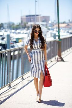 Rachel Parcell of Pink Peonies wears a striped shirt dress, nude wedge, oversized sunglasses, and a red tote bag