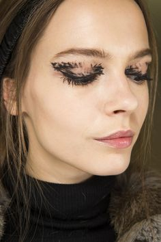 Fall 2015 beauty - Peter Philips made eyes the focus at Fendi, with layer upon layer of black mascara, and painterly stripes across the lids for a feathered appearance. A subtle gloss was applied to lips.