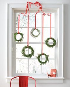 mini wreaths hanging from the window
