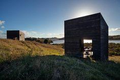I due capanni dei due amici si trovano in una remota regione della Nuova Zelanda. Stessa architettura, ambienti su misura: uno in legno scuro, l'altro in legno chiaro