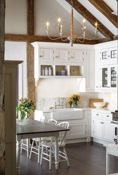 White modern farmhouse kitchen decor ideas: A breathtaking white kitchen with traditional decor and farmhouse style. Rustic wood beams, farm sink, and shaker style cabinets. #whitekitchen #farmhousekitchen #vaultedceiling #traditional #modernfarmhouse