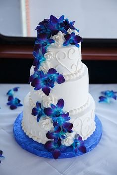 Round White Wedding Cake with Swirls and Blue Orchid Flowers wedding cakes blue Waterfront Tampa Bay Wedding Round Up Royal Blue Wedding Cakes, Wedding Cakes With Flowers, Wedding Blue, Trendy Wedding, Quirky Wedding, Cascading Flowers, Fresh Flowers, Royal Blue Weddings, Floral Wedding