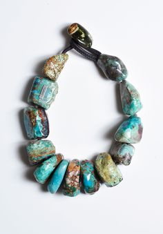 Chunky turquoise necklace by Monies. Large, partly polished rough turquoise matrix beadsknotted between stones; stone and leather closure.