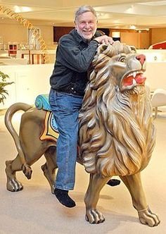Duane S. Perron, 73, sits on a circa 1890 Gustuv Denzel lion named Dandy Lion which will be on display at the Alden B. Dow Museum of Science & Art.