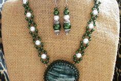 Serafinit patrí medzi anjelske kameňe, dávajú duši harmóniu a pokoj. Zakompovaný je šitou technikou japonským rokajlom, zdobený pravými riečnymi perlami, ktoré podtrhujú čaro a jemnosť drahokamu. Prívesok je zavesený na šitej retiazke z voskových perál a rokajlu. Zapínanie tvorí zaujímava filigránová kvetina, ktorá podtrhuje prepychovosť celého náhrdelníka  Náušničky sú zavesené na ozdobných nitoch. Pozostávajú z rovnakého materiálu a doplnené sú masívnymi kovovými kaplíkmi