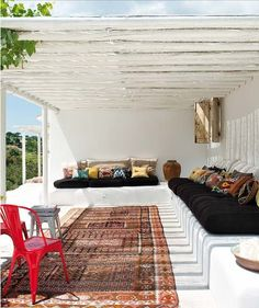Delightful outdoor living with white washed walls and floor, bright pillows for seating comfort and lovely area rug that adds comfort and style!