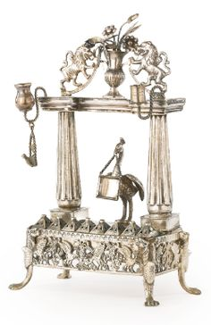 A Silver Portico and Peacock Hanukah Lamp, 19th century. The platform is centered by a peacock, with fluted columns. - Sotheby's
