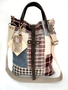PATCHWORK TOTE - This bag is loaded with vintage goodness! Among the textiles here are authentic German Kelsch, handwoven linen plaid, both dating to the 1800s, antique ticking, denim, homespun plaid cotton, and more!! The bag is lined with cotton canvas ticking with blue stripes and a zippered compartment to securely store your smaller items. The bag closes with a brass snap closure as well as a leather strap. The handles are thick 8/9 oz leather and the shoulder strap is 1.5 heavy canvas…