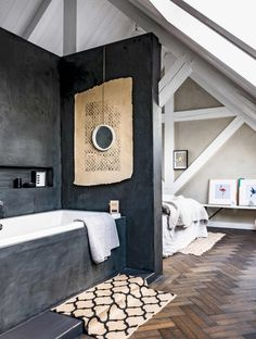 en-suite bathroom to an attic bedroom - white exposed beams, chevron parquetry timber floor